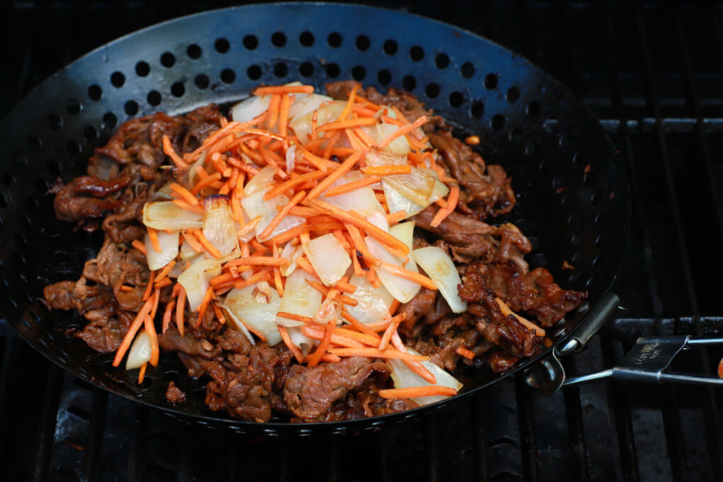 Close up of bulgogi beef in a grill basket, topped with onions and carrots.