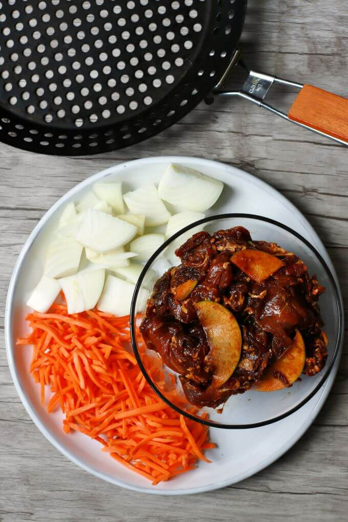 Marinating beef with raw onions and carrots on a white platter.
