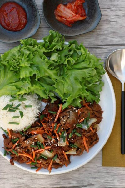 A platter containing cooked bulgogi beef, lettuce leaves, and rice.