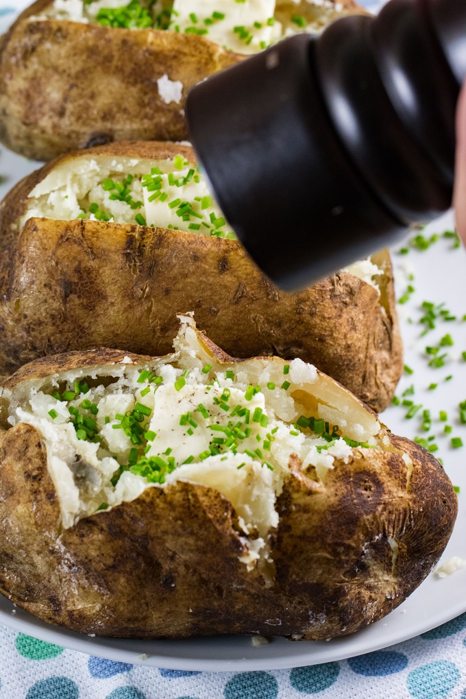 Grilled Baked Potatoes on a white plate with butter, chives and a pepper grinder