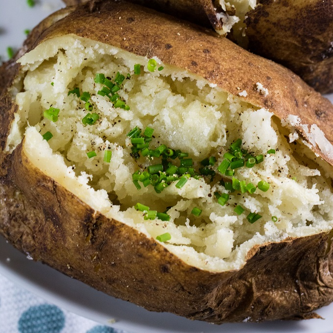 Grilled baked potato with chives butter and black pepper on it.