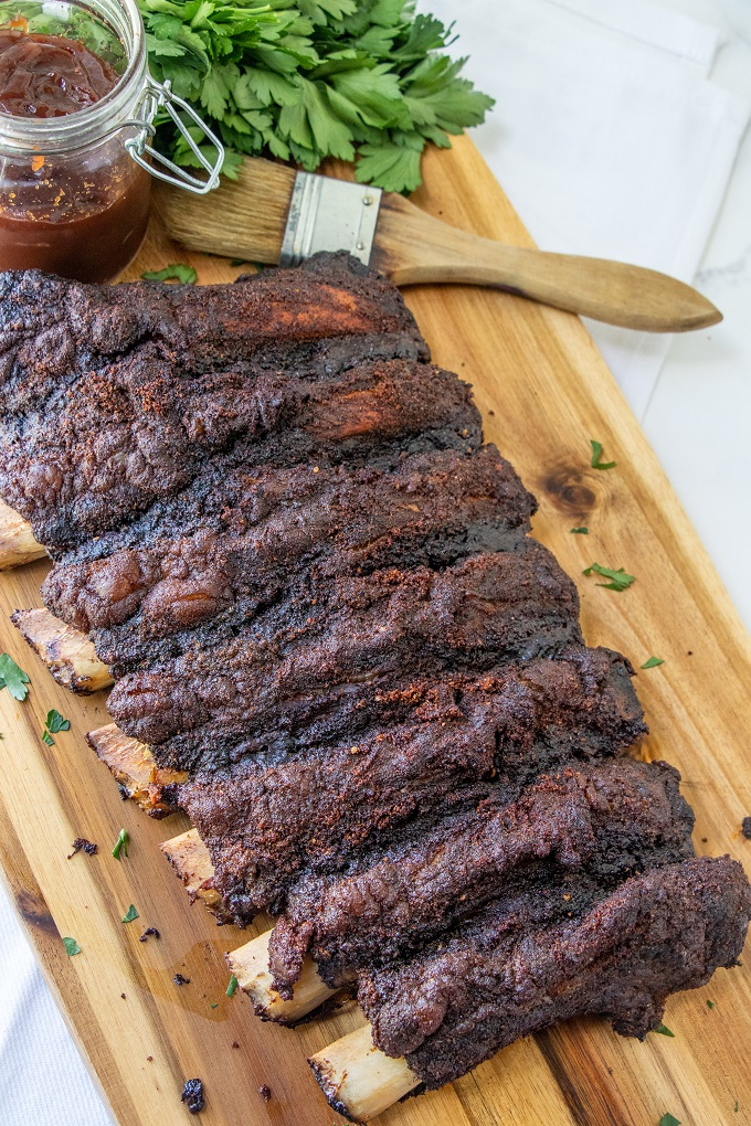 Smoked rack of beef ribs on a wooden board with a brush and a jar of BBQ sauce