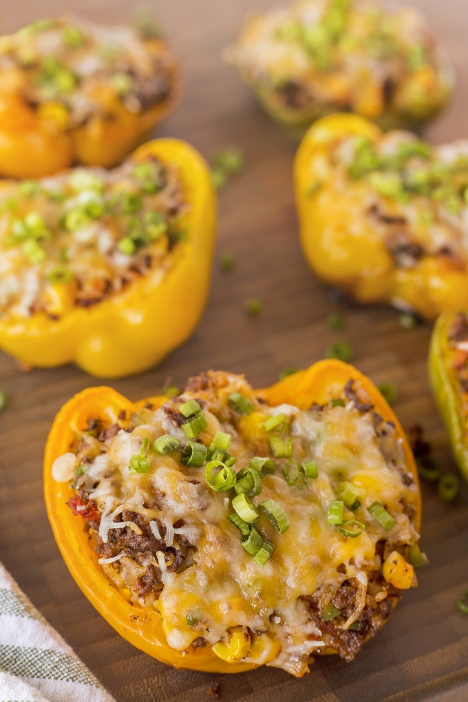 Grilled stuffed pepper halves ona wooden board with melted cheese and green onions slices on top