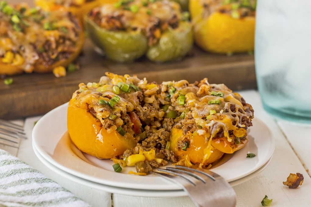 Grilled stuffed pepper cut in half on a white plate with a fork