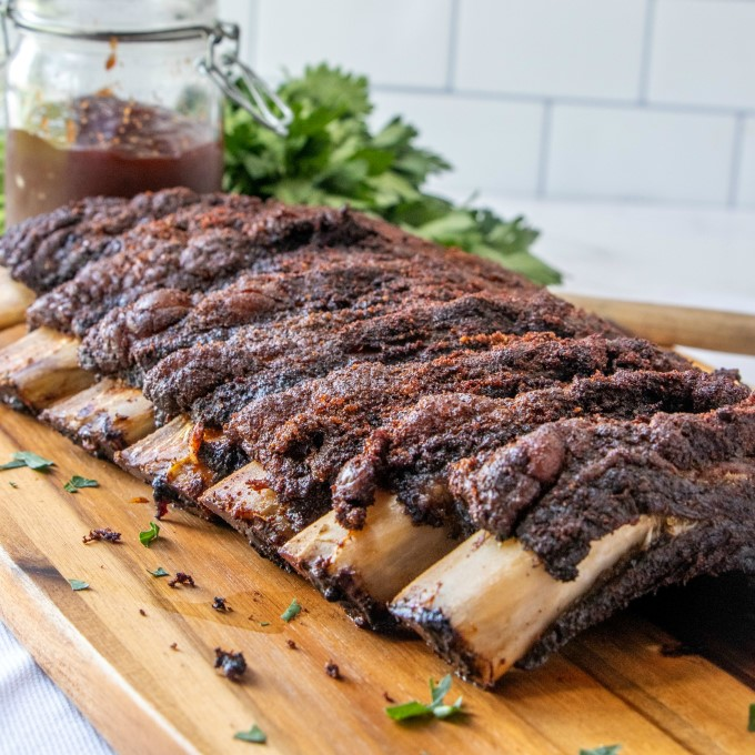 Full rack of smoked beef ribs on a wooden board