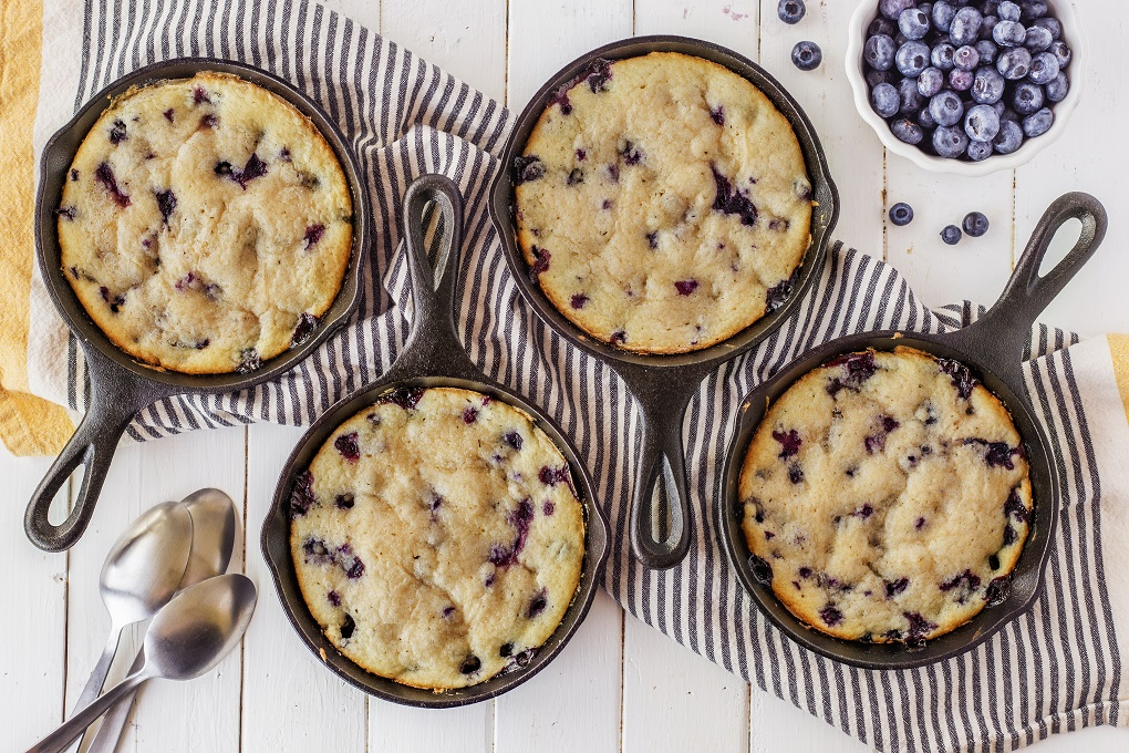 4 cast iron skillets full of Lemon Blueberry cake with a bowl of fresh blueberries and 4 spoons on a wooden table