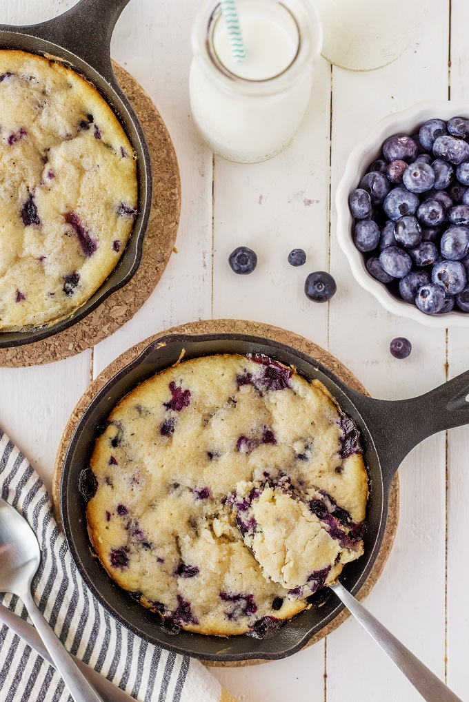 Lemon blueberry cake in a cast iron skillet with a spoonful scooped out.