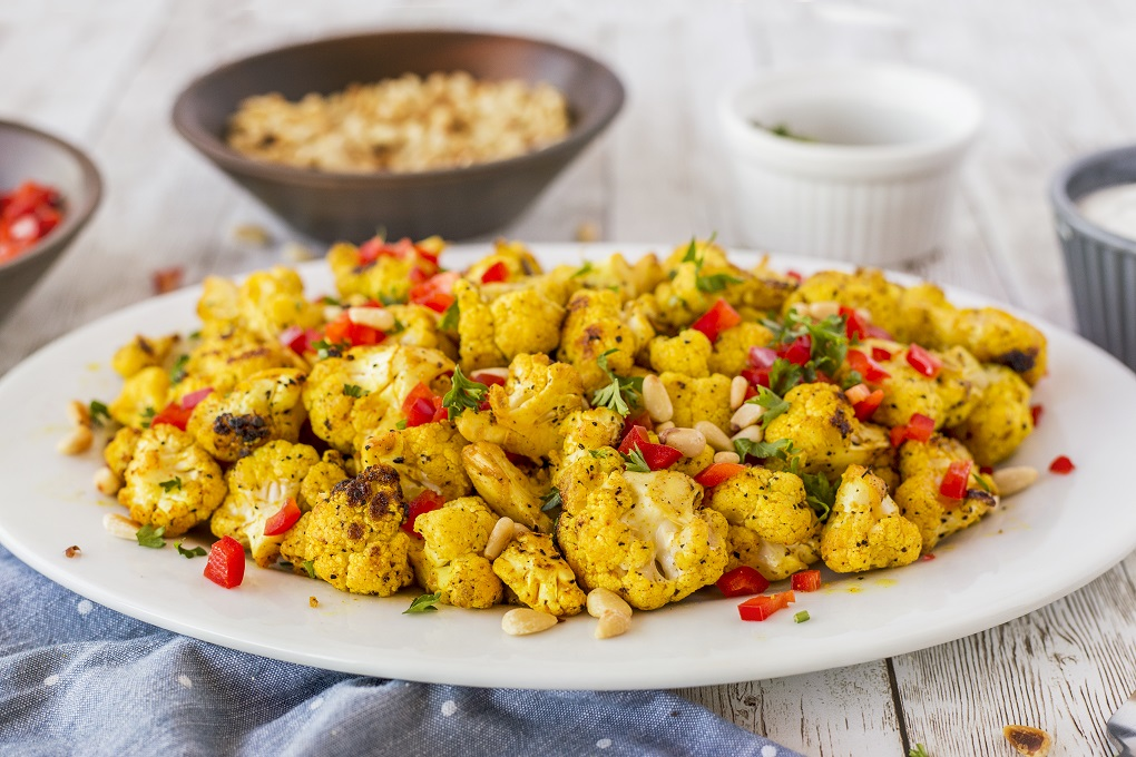 White platter of curry grilled cauliflower with toasted pine nut and diced red pepper of top