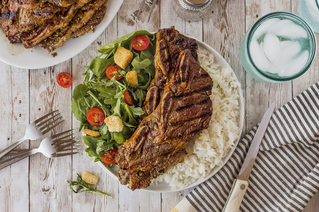 Grilled Korean short ribs on a white plate with white rice and a green salad on a rustic table