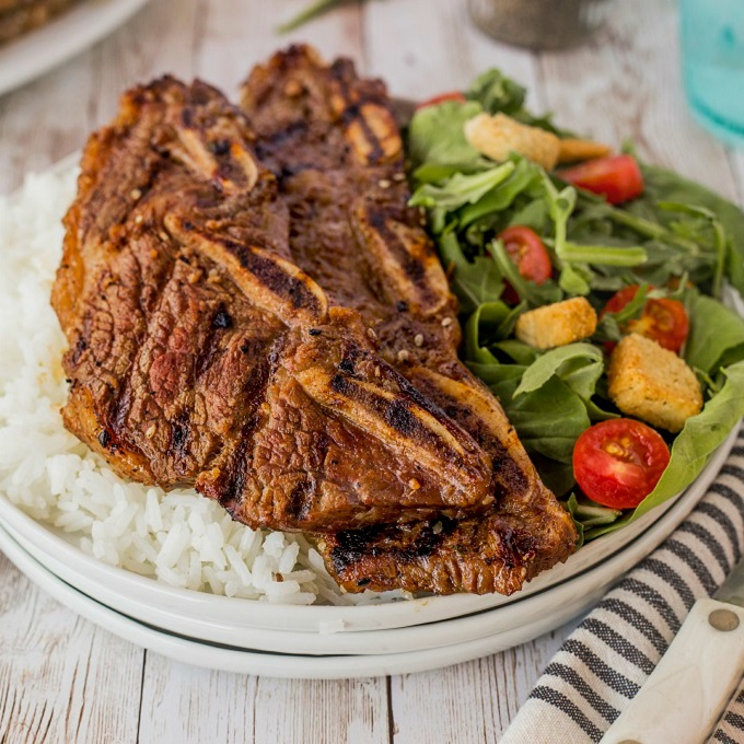 Grilled Koprean beef short ribs on a white plate with white rice and a fresh green salad