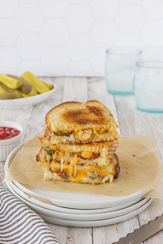 Jalapeno popper grilled cheese cut in half and stacked on a white plate with gooey cheese in front