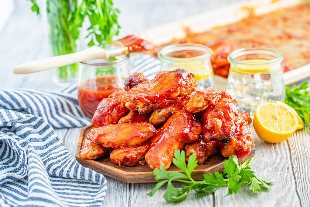 Smoked chicken wings with bourbon BBQ sauce stacked on a wooden platter