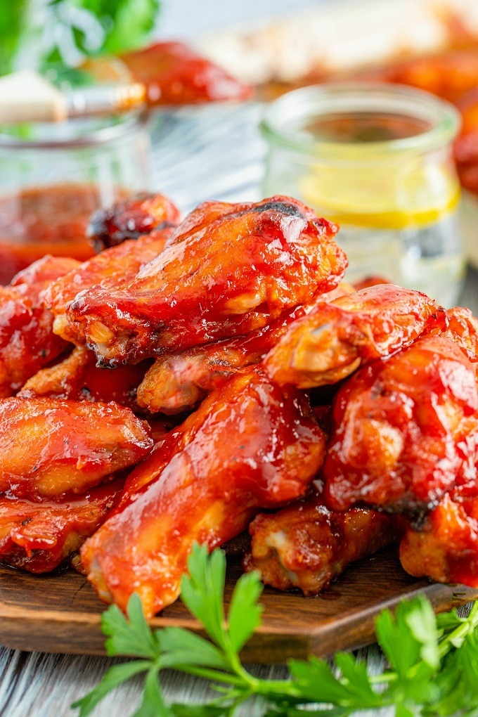 Smoked chicken wings with bourbon BBQ sauce stacked on a wooden board with parsley