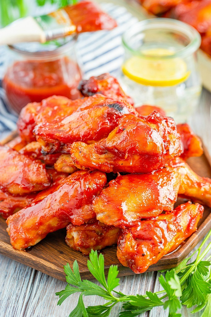 Smoked chicken wings covered in bourbon BBQ sauce stacked on a wooden platter with parsley.