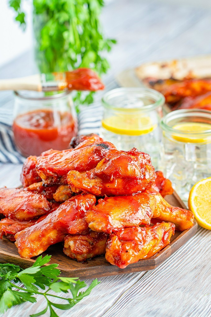 Close up of smoked chicken wings covered with bourbon BBQ sauce stacked on a wooden platter.