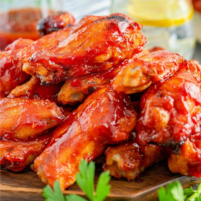 Close up picture of smoked chicken wings with bourbon BBQ sauce stacked on a wooden plate.