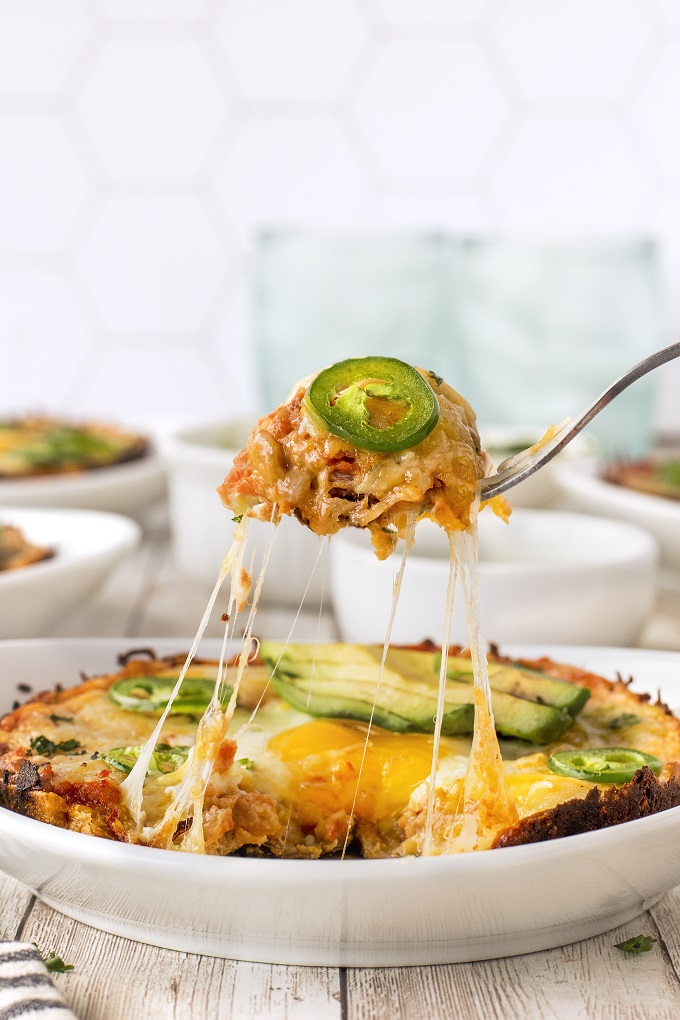 A fork full of huevos rancheros with a slice of jalapeno being taken from the plate. The cheese is stretching from the plate the the fork.