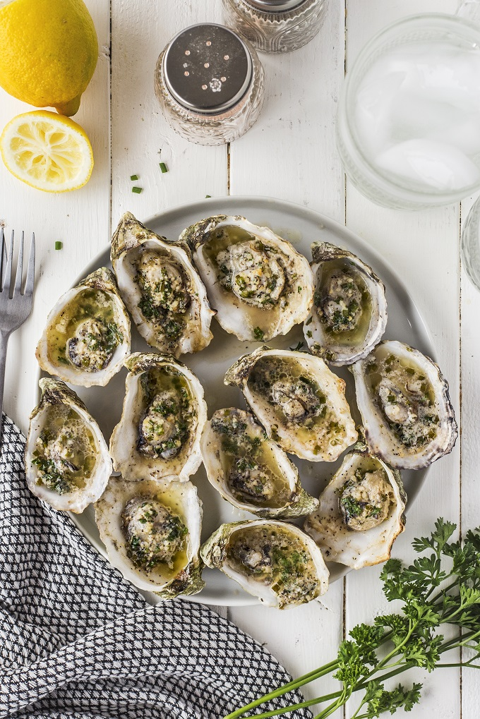 Grilled oysters on a white platter with a half a lemon on a white wooden table