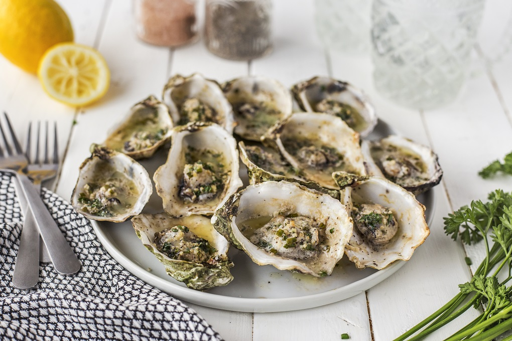 grilled oysters on a white platter with lemon slice, parsley and 2 forks around the plate