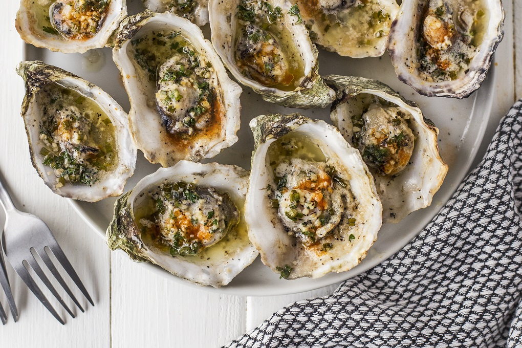 Grilled oyster on a white plate with garlic butter sauce and hot sauce on them