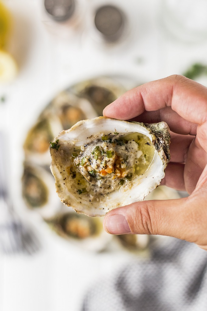persons hand holding a grilled oyster on the half shell with butter, garlic, chives, and drop of hot sauce