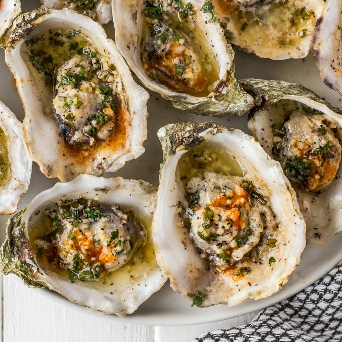 Grilled oysters on a white plate with garlic, butter chives and hot sauce