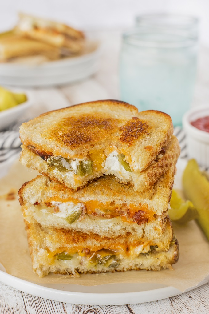 Jalapeno popper grilled cheese sandwiches cut in halk and stack on a white plate, the top sandwich as a bite our of it!