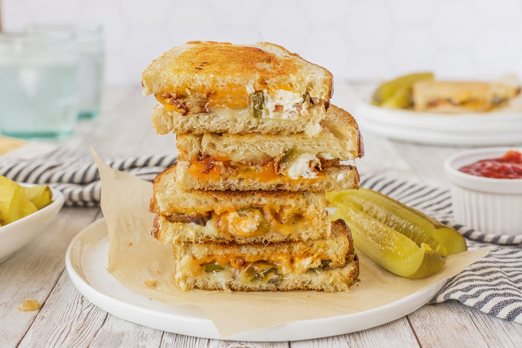 Jalapeno popper grilled cheese cut in half and stacked up sitting on a white plate with 2 pickles.