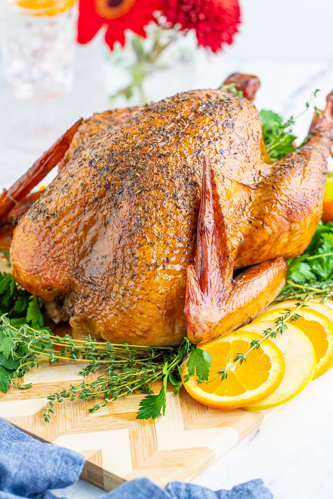Whole smoked turkey with fresh herbs and orange slices.