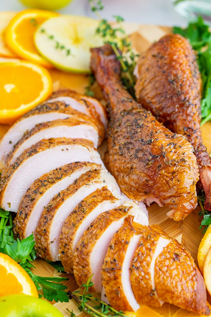 Sliced smoked turkey breast and drum sticks on a wooden cutting board with orange slices and parsley