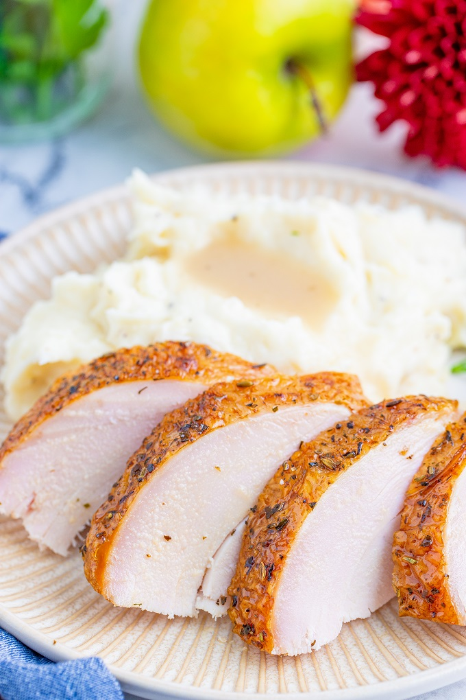 Sliced smoked turkey breast on a white plate with mashed potatoes in the background.
