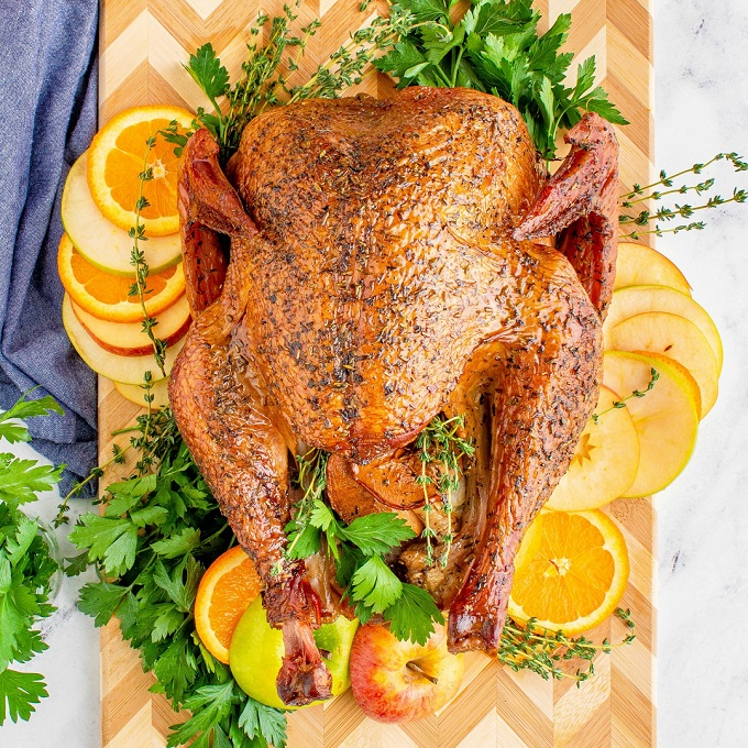 Whole smoked turkey on a wooden cutting board with fresh herbs and apple and orange slices.