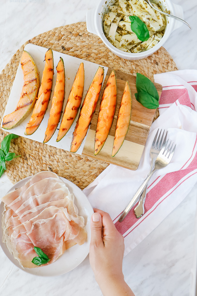 Grilled wedges of cantaloupe with a plate of prosciutto and mozzerella in a white dish.