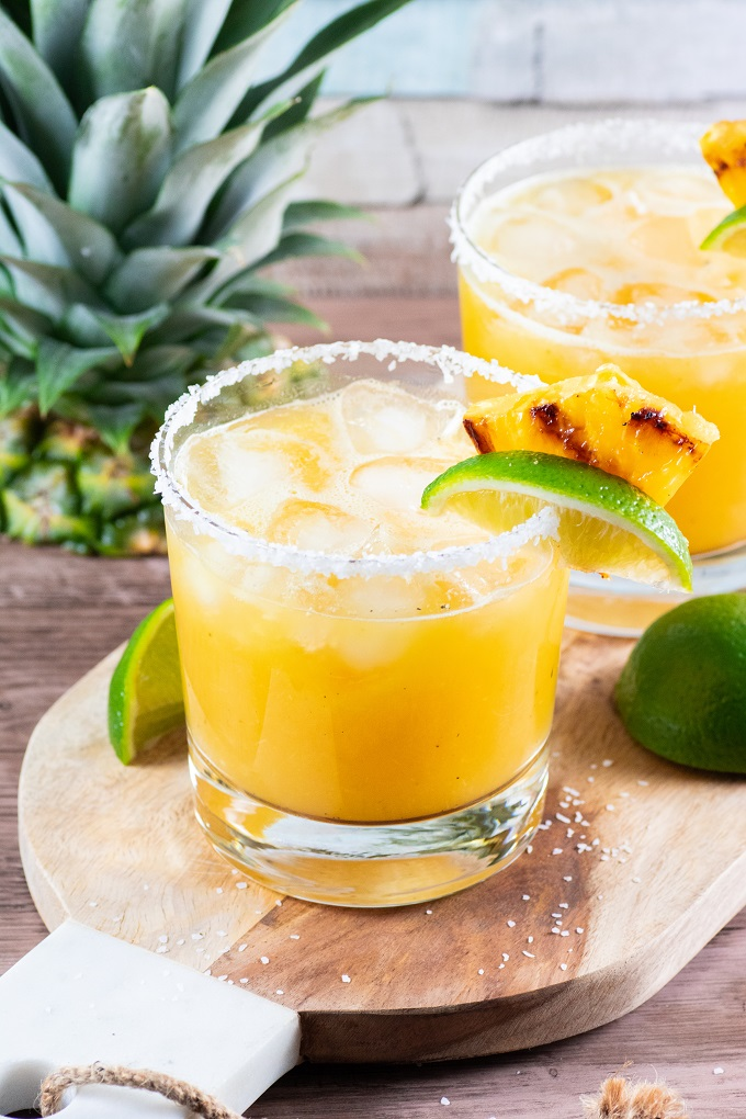 Grilled pineapple margarita with a salted rim on a wooden board garnished with a wedge of lime and a piece of grilled pineapple.