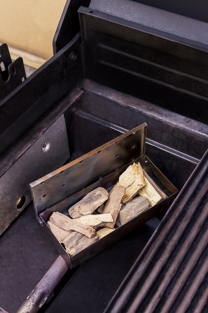Metal smoker box filled with wood chunks on a gas grill