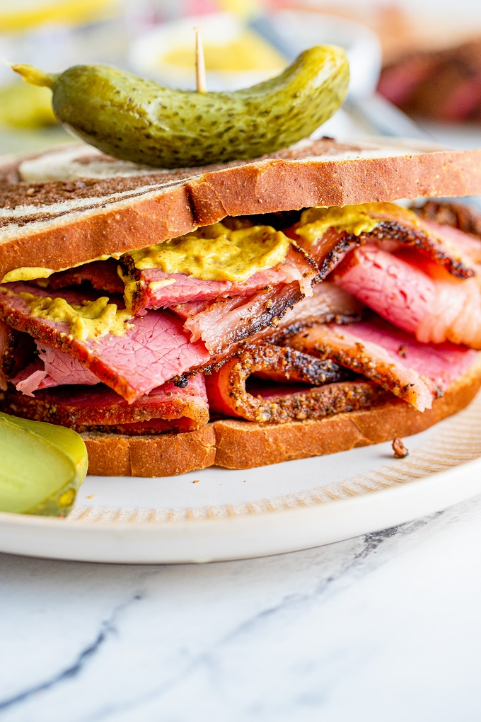 Sliced pastrami on marble rye bread with a pickle on top held by a toothpick with mustard on the sandwich.