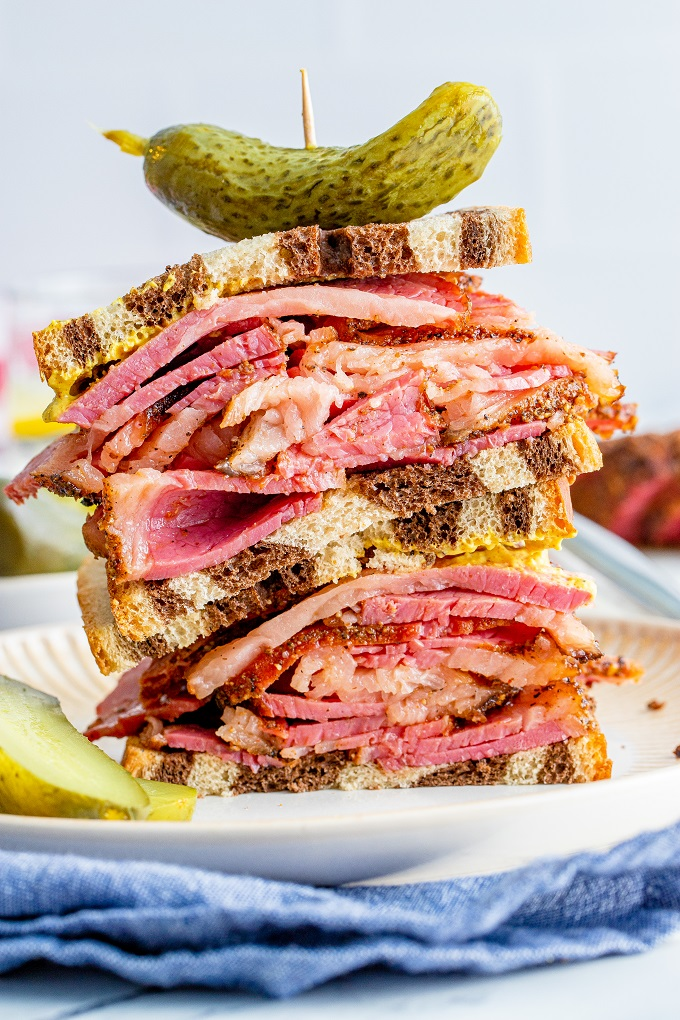 Smoked pastrami sliced and piled high on marbled rye bread slices with mustard and a dill pickle on top