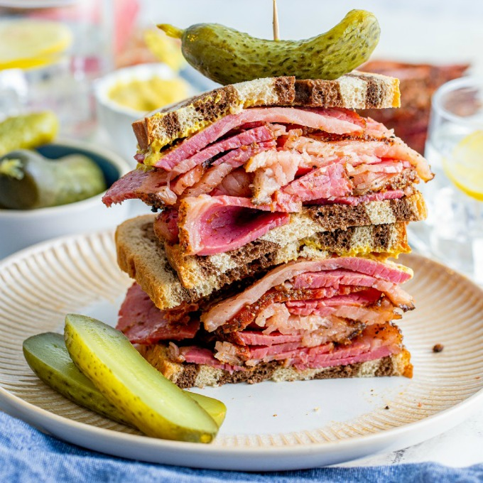 2 half sandwiches of thinly slices pastrami on marble rye bread staked on top of each other on a white plate with slices of pickles.