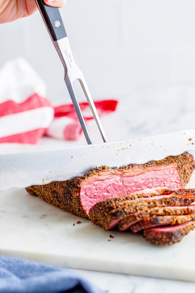 A knife is slicing pieces off the smoked meat brisket on a white cutting board