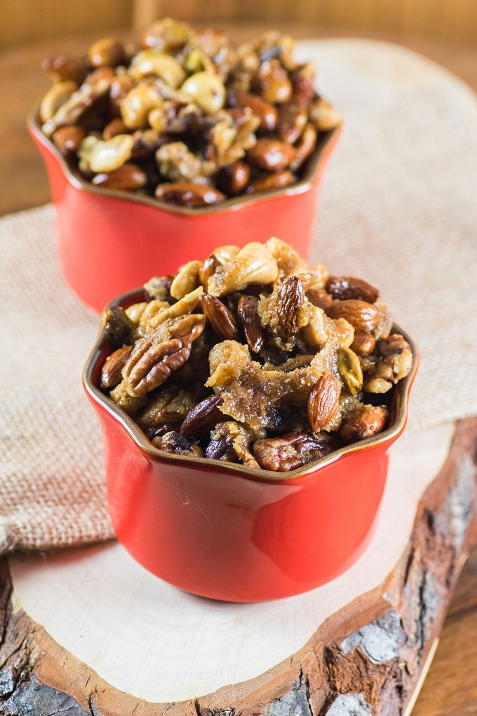 Two small bowls of hickory smoked mixed nuts on a wooden board.