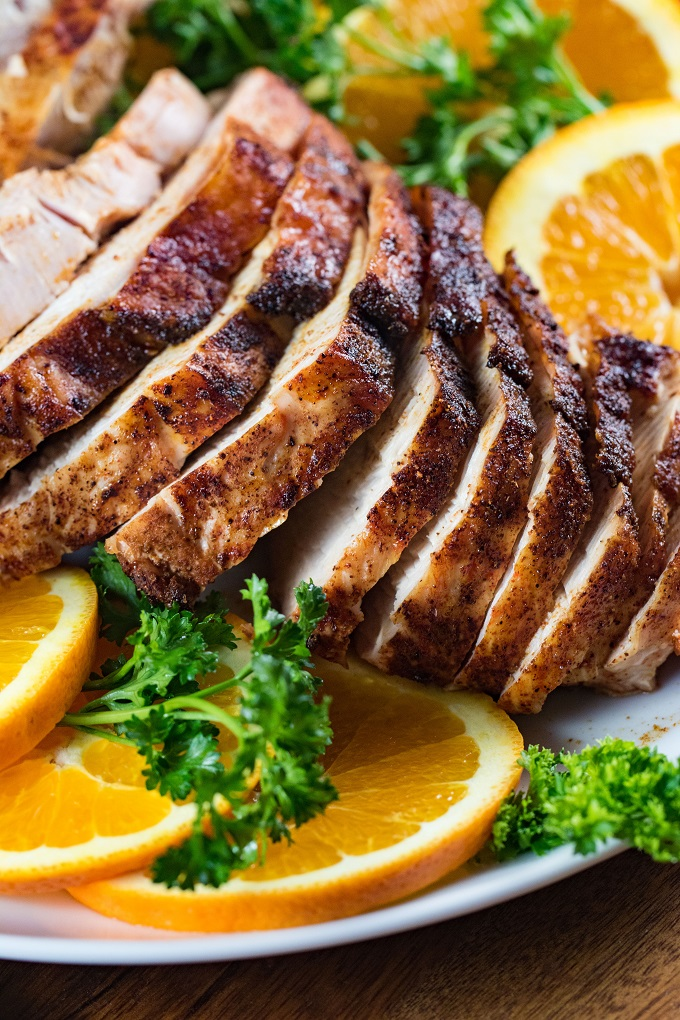 Sliced southwest grilled turkey breast on a white platter with parsley and orange slices.