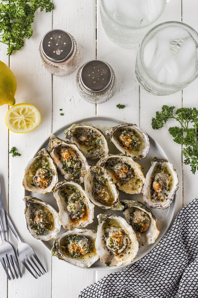 Grilled Garlic herb buttered oysters on the half shell arranged on a white platter.