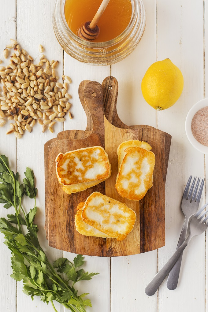 Slices of smoked and fried halloumi cheese stacked in twos on a small wooden cutting board