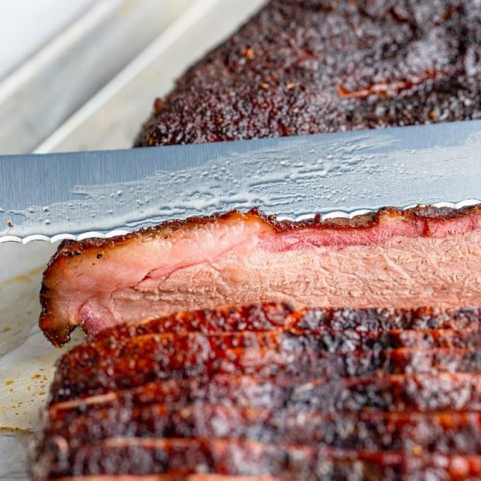 close up of a knife slicing smoked brisket