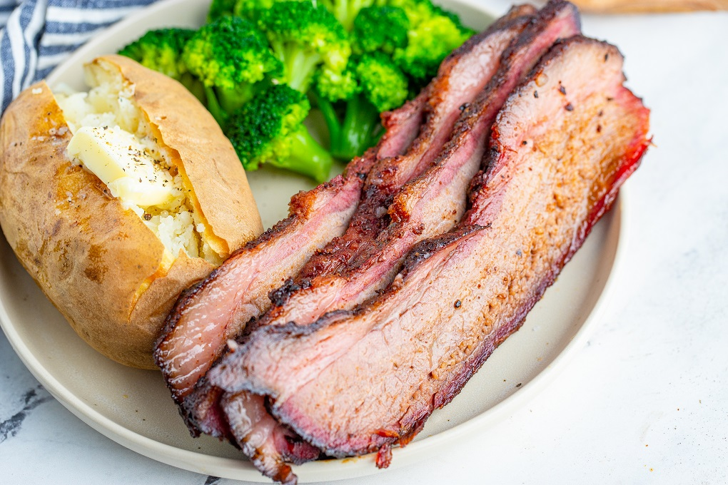 Smoked brisket slices on a white plate with a baked potato and broccoli.