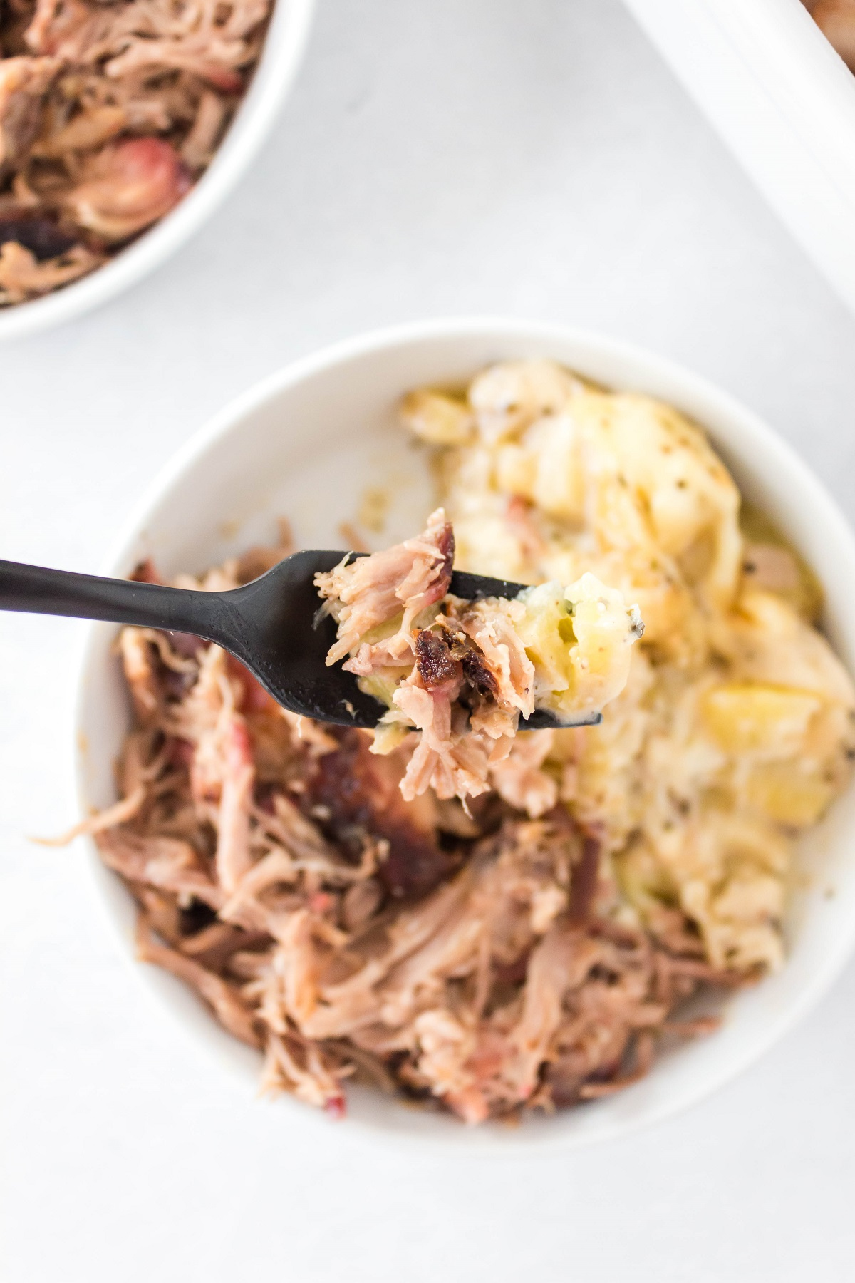 Fork full of pulled pork over a white bowl filled with pulled pork and mashed potatoes