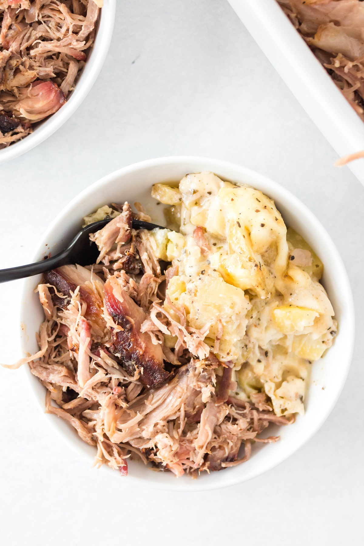 Pulled pork in a small white serving bowl with mashed potatoes.