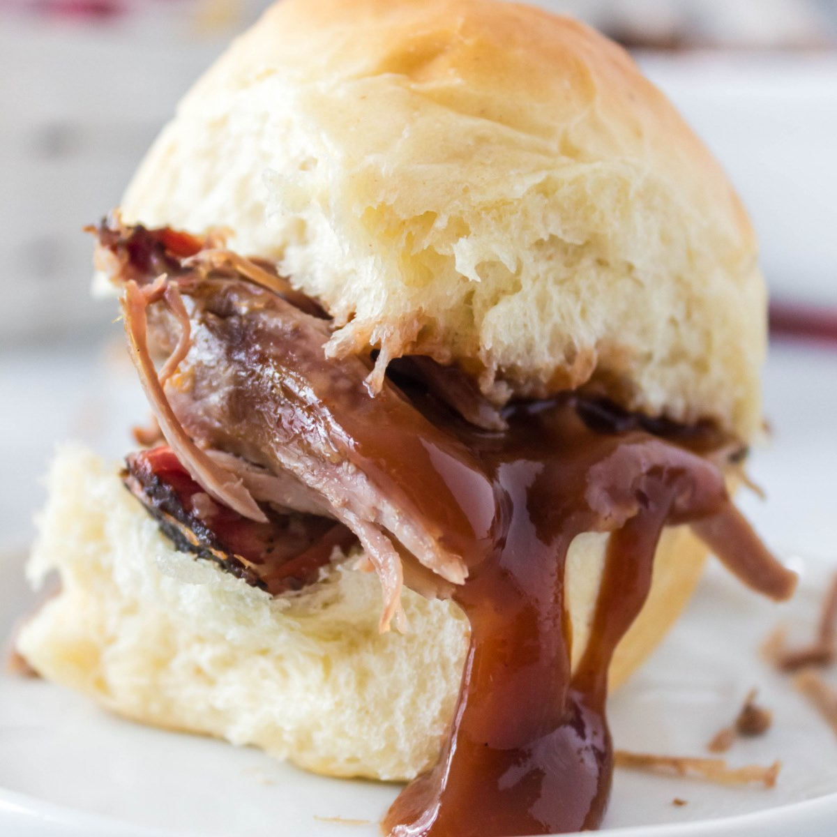 Shredded smoked BBQ pulled pork on a bun with BBQ sauce dripping down the side of the bun onto a small white plate.