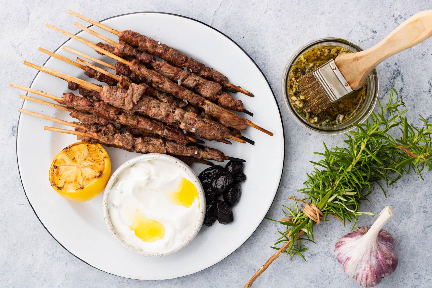 Grilled spiedini on a white platter with tzatziki sauce, grilled lemon half and prunes