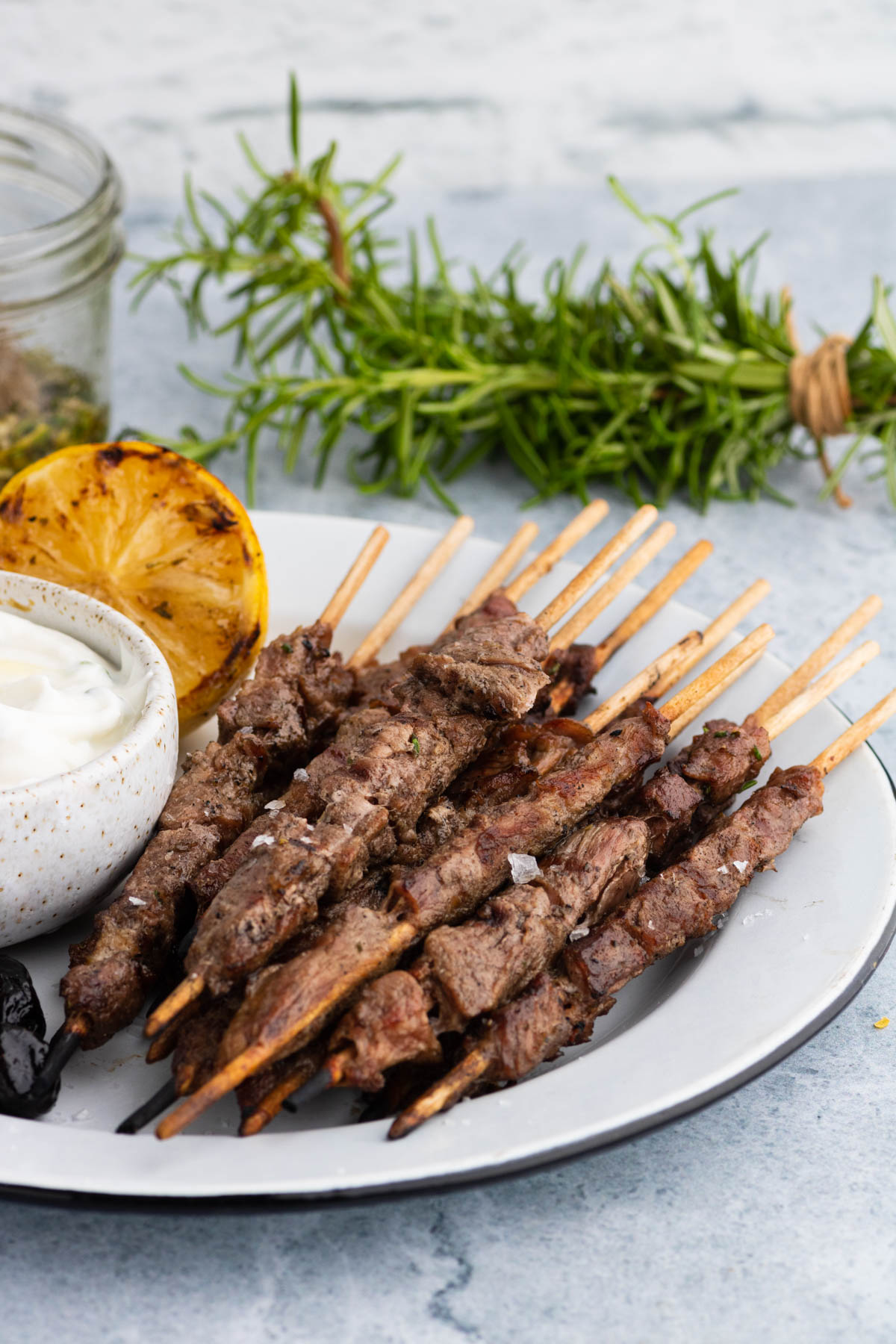 Grilled Spiedini skewers on a white plate with grilled half lemon and dipping sauce